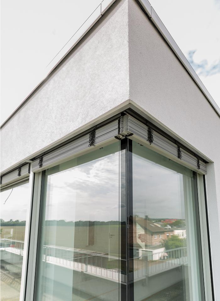 eckfenster aus glas mit rolladen